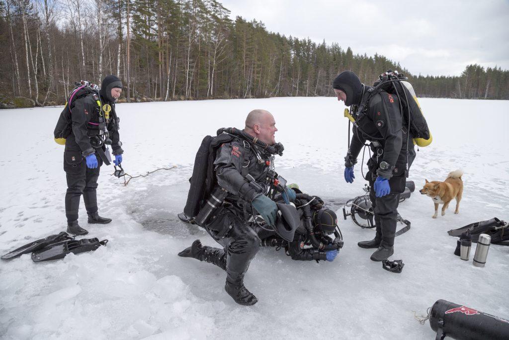Tarja Kokko on nousemassa avannosta Heikki Kokon ja Jari Lindbergin avustuksella. Varusteet painavat kymmeniä kiloja. Kuva: Pekka Tuuri.