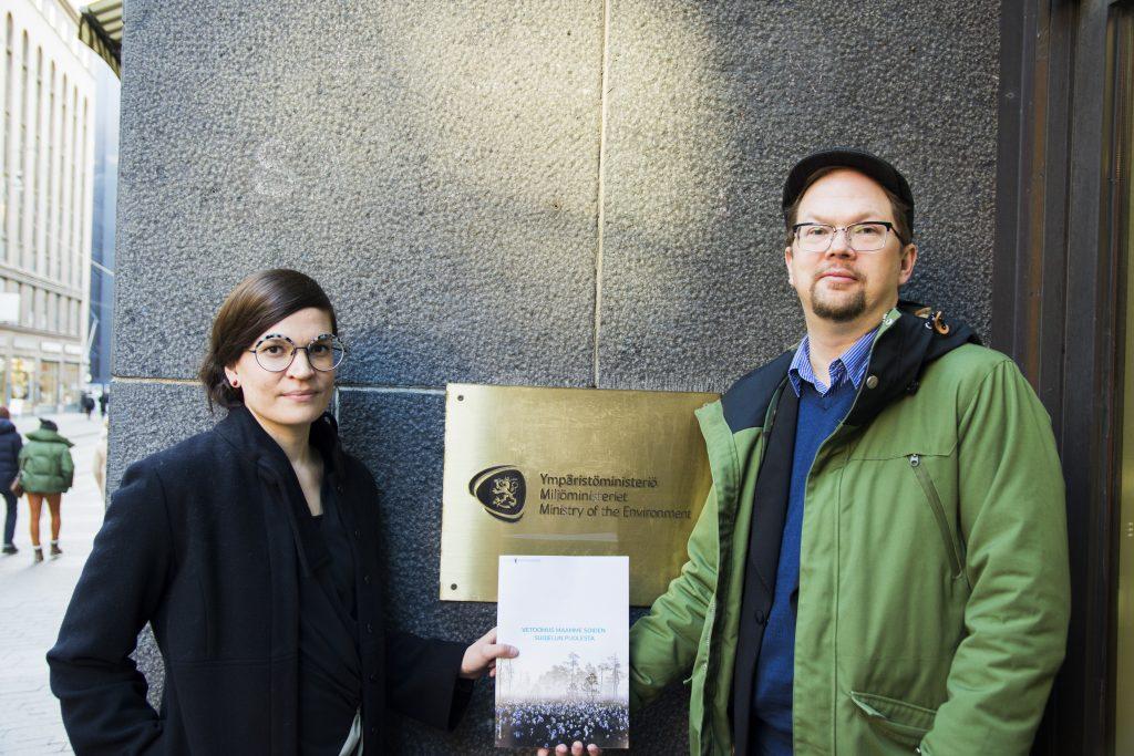 Kuvassa on Paloma Hannonen ja Harri Hölttä, jotka seisovat ympäristöministeriön kyltin edessä pitäen suovetoomusta. Kuva: Oona Lohilahti