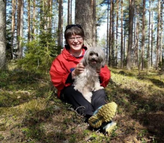 Anne Laine metsässä koiransa kanssa.