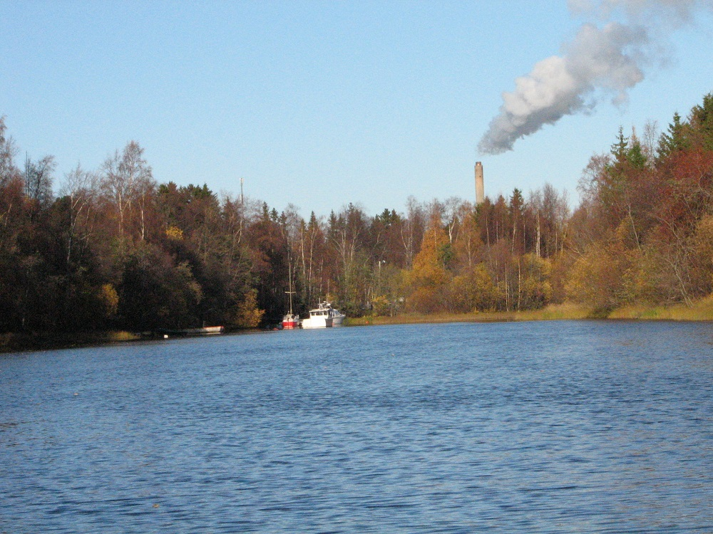 Toppilan lämpövoimalan vanha savupiippu jokimaisemassa.